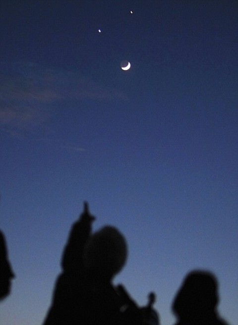 Star gazers look at the crescent moon below Jupiter (top) and Venus in Kathmandu December 1, 2008.   REUTERS/Gopal